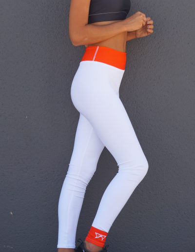 Morgan Cryer modeling the right side view of the white Goblin Yoga/Surf Leggings by Shark Tooth Surf Co.